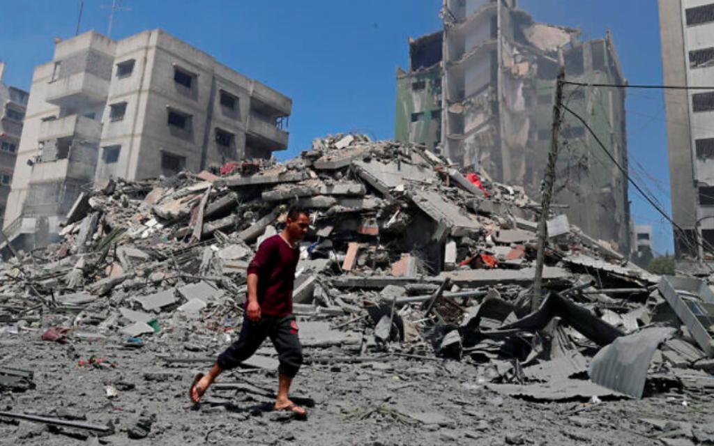 Un homme passe devant les décombres de l'immeuble résidentiel de Yazegi qui a été détruit par une frappe aérienne israélienne menée à Gaza City en représailles aux roquettes tirées par le Hamas, dimanche 16 mai 2021. (Crédit : AP Photo / Adel Hana)