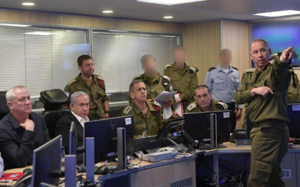 Le ministre de la Défense Benny Gantz, le Premier ministre Benjamin Netanyahu et le chef de Tsahal Aviv Kohavi dans un centre de commandement de l'armée de l'air israélienne alors que l'armée de l'air israélienne bombarde le réseau de tunnels du Hamas à Gaza pendant la nuit du jeudi au vendredi 13-14 mai 2021 (Crédit : Kobi Gideon / GPO)