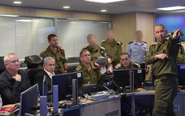 Le ministre de la Défense Benny Gantz, le Premier ministre Benjamin Netanyahu et le chef de Tsahal Aviv Kohavi dans un centre de commandement de l'armée de l'air israélienne alors que l'IAF bombarde le réseau de tunnels du Hamas à Gaza pendant la nuit du jeudi au vendredi 13-14 mai 2021 (Crédit : Kobi Gideon / GPO)