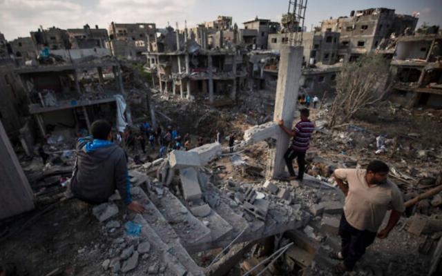 Des Palestiniens inspectent des bâtiments détruits à la suite de frappes aériennes israéliennes pendant la nuit à Beit Hanoun, dans le nord de la bande de Gaza, le 14 mai 2021 (Crédit : AP Photo / Khalil Hamra)