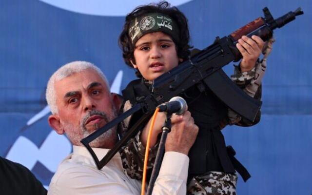 Le chef du Hamas, Yahya Sinwar, tient l'enfant d'un membre des Brigades Ezzedin  Al-Qassam, tué lors des récents combats avec Israël, le 24 mai 2021. (Crédit : Emmanuel Dunand/AFP)