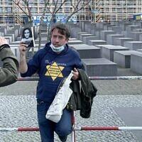 Un homme manifeste contre les restrictions entraînées par le coronavirus avec une étoile jaune et une photo d'Anne Frank aux abords du mémorial de la Shoah, à Berlin. (Crédit :  @ZSKberlin/Twitter via JTA)