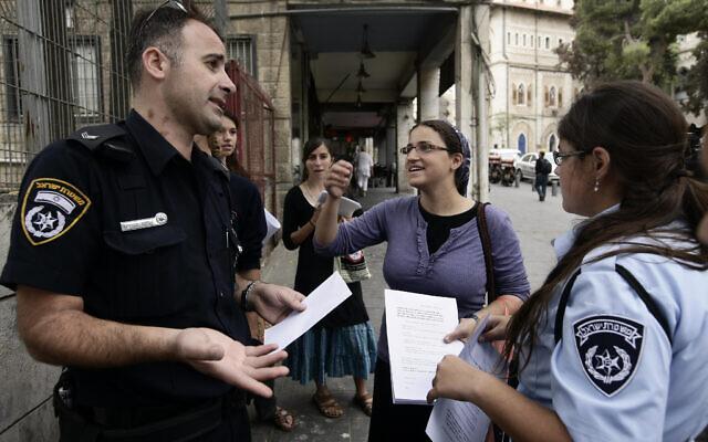 Ayala Ben Gvir, au centre, épouse du politicien de droite Itamar Ben Gvir, discute avec la police alors qu'elle se tient avec d'autres manifestants de droite devant un lycée de Jérusalem distribuant des tracts contre une cérémonie de commémoration du premier ministre Yitzhak Rabin, assassiné 14 ans plus tôt, le 29 octobre 2009. (Crédit : Abir Sultan/FLASH90)