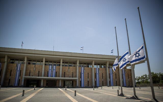 Les drapeaux israéliens en berne en mémoire des victimes de la bousculade du mont Meron à la Knesset, à Jérusalem, le 2 mai 2021. (Crédit : Yonatan Sindel/Flash90)