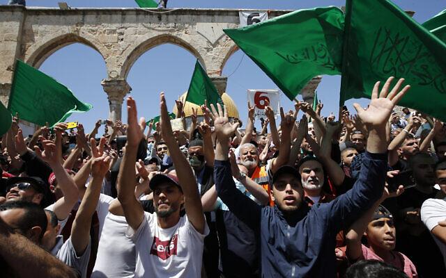 Des Palestiniens brandissent des drapeaux du groupe terroriste du Hamas après les prières de l'après-midi au cours du dernier vendredi du mois du Ramadan, sur le mont du Temple, dans la Vieille Ville de Jérusalem, le 7 mai 2021. (Crédit : Jamal Awad/Flash90)