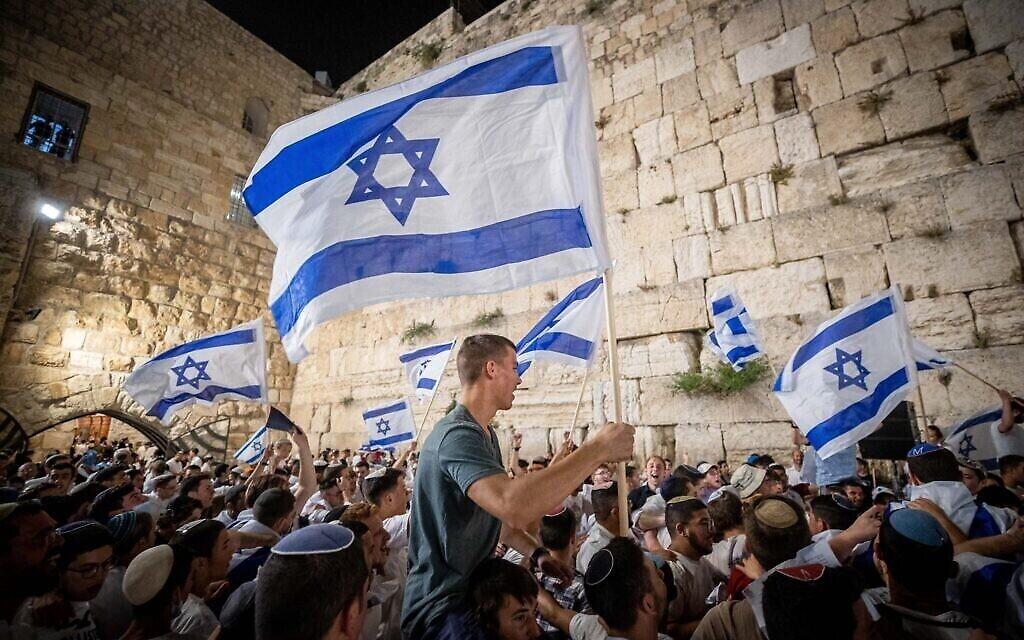 Des Juifs dansent avec des drapeaux d'Israël au mur Occidental, à la veille de Yom Yeroushalayim, le 9 mai 2021. (Crédit : Yonatan Sindel/Flash90)