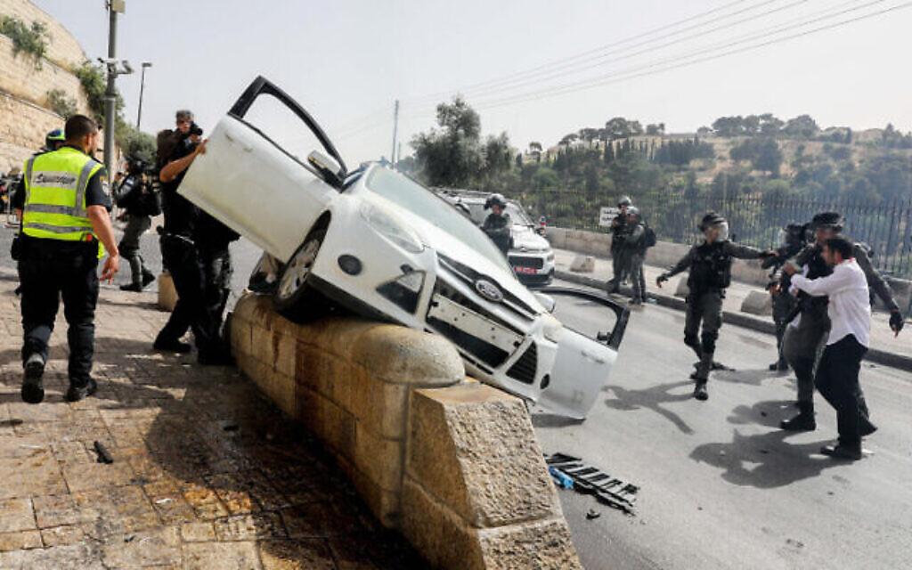 Les forces de sécurité israéliennes devant une voiture qui a été la cible de jets de pierres à l'extérieur de la vieille ville de Jérusalem, le 10 mai 2021. (Crédit : Olivier Fitoussi/Flash90)