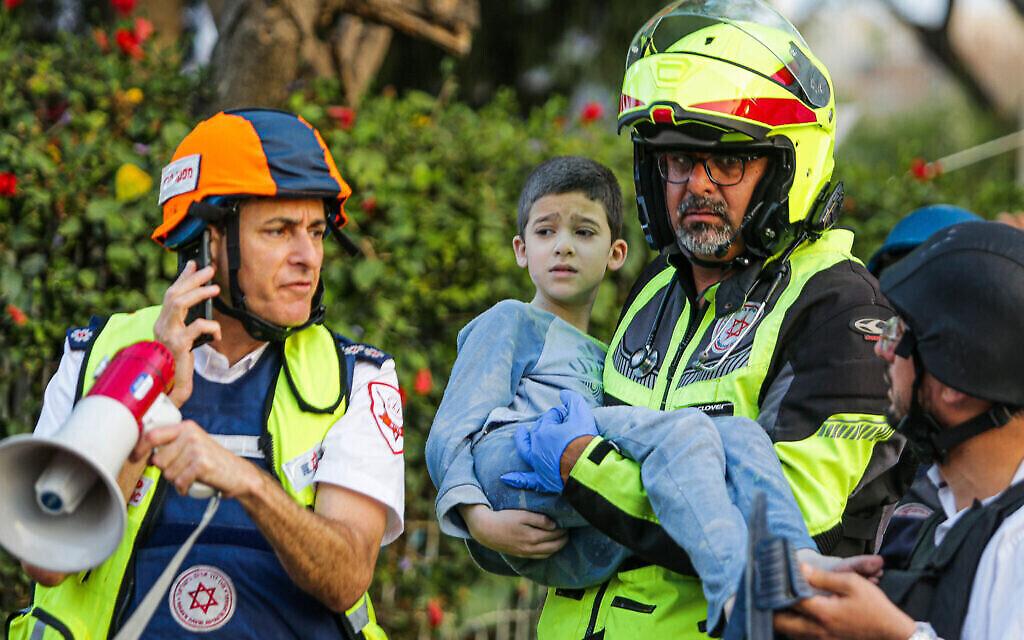 Un secouriste transporte un enfant blessé sorti d'un immeuble d'appartement touché par une roquette tirée depuis Daza à Ashkelon, le 11 mai 2021. (Crédit : Flash90)