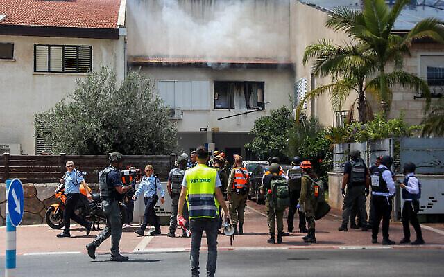 Les forces de sécurité israéliennes devant une maison d'Ashdod touchée par une roquette tirée depuis la bande de Gaza, le 11 mai 2021. (Crédit : Flash90)