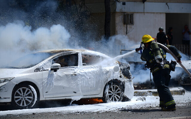 Un pompier éteint un feu sur une voiture causé par une roquette, à Ashkelon, le 11 mai 2021. (Crédit : Tomer Neuberg/Flash90)