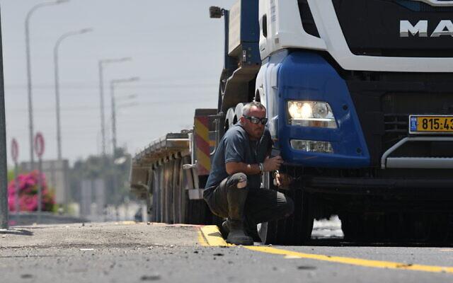Un chauffeur de camion s'abrite pendant une alerte à la roquette près d'Ashkelon, le 12 mai 2021. (Crédit : Gili Yaari/Flash90)