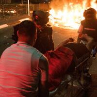 Photo d'illustration : Des secouristes évacuent un homme blessé lors d'affrontements entre Arabes et Juifs à Akko, dans le nord d'Israël, le 12 mai 2021. (Crédit : Roni Ofer/Flash90)