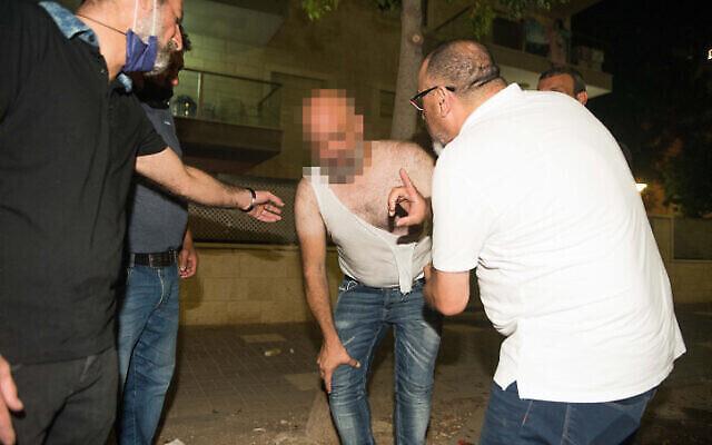 Un homme blessé lors d'affrontements entre Arabes et Juifs à Akko, dans le nord d'Israël, le 12 mai 2021. (Crédit : Roni Ofer/Flash90)