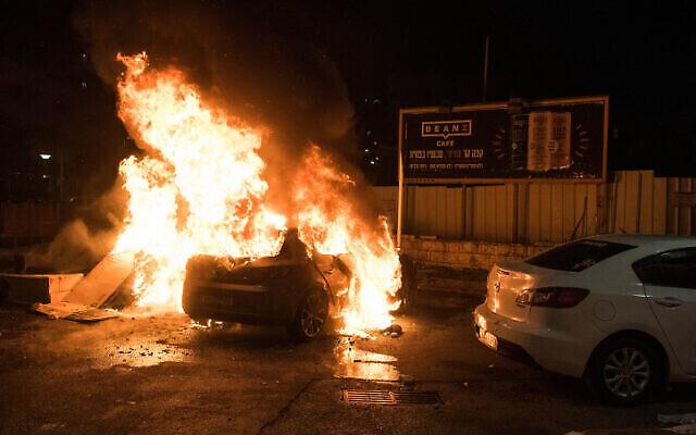 Une voiture en feu suite à des affrontements entre Arabes et Juifs à Akko, dans le nord d'Israël, le 12 mai 2021. (Crédit : Roni Ofer/Flash90)