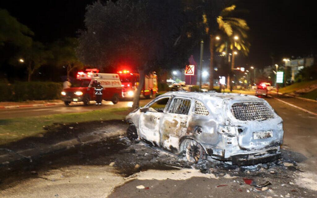 Une voiture incendiée par des résidents arabes pendant des émeutes et des affrontements entre résidents arabes et juifs à Lod, dans le centre d'Israël, le 12 décembre 2021. (Crédit : Yossi Aloni/FLASH90)