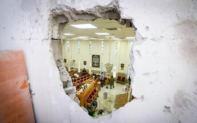 Les forces de sécurité dans une synagogue frappée par une roquette tirée depuis la bande de Gaza à Ashkelon, dans le sud d'Israël, le 16 mai 2021. (Crédit : Avi Roccah/Flash90)