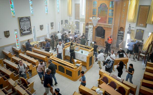 Des fidèles nettoient l'intérieur d'une synagogue endommagée suite à un tir de roquette de Gaza à Ashkelon, le 16 mai 2021. (Crédit : Avi Roccah/Flash90)