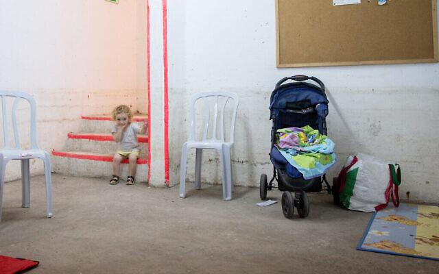 Une jeune enfant à l'intérieur d'un abri anti-bombes à Tel Aviv alors que des barrages de roquettes de Gaza pleuvent sur la ville, le 16 mai 2021 (Crédit : Miriam Alster / Flash90)