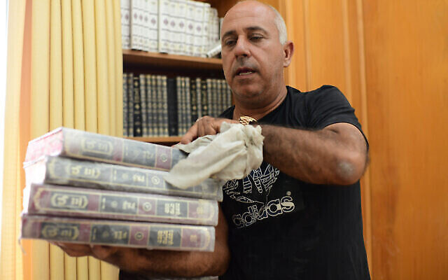 Des fidèles nettoient l'intérieur d'une synagogue endommagée suite à un tir de roquette de Gaza à Ashkelon, le 16 mai 2021. (Crédit : Tomer Neuberg/Flash90)
