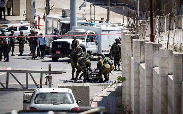 Les soldats israéliens sur le site où un Palestinien a tenté d'attaquer des militaires en ouvrant le feu et en tentant de jeter une bombe avant d'être abattu, à Hébron, le 18 mai 2021. (Crédit : Wisam Hashlamoun/FLASH90)