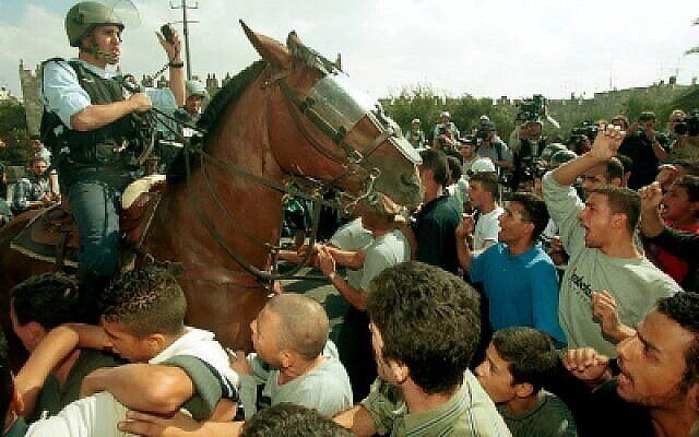 Un policier à cheval au milieu d'une foule d'Arabes israéliens lors d'affrontements au début de la Seconde Intifada, le 20 octobre 2000. (Flash90)