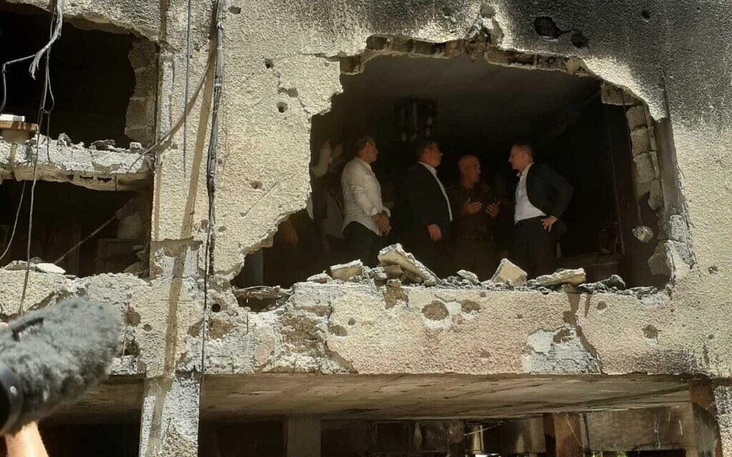 Le ministre allemand des Affaires étrangères, Heiko Maas, visite un bâtiment à Petah Tikva touché par une roquette tirée depuis la bande de Gaza, le 20 mai 2021. (Crédit : Miri Shimonovitch).
