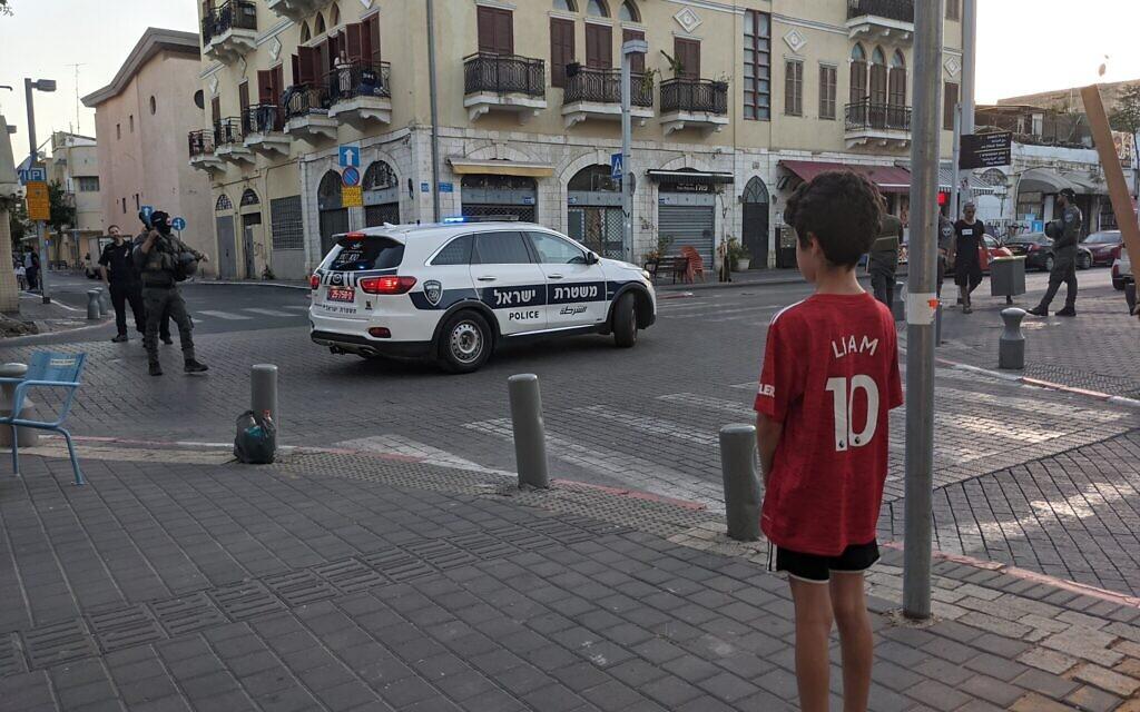 Un enfant regarde les forces de police locales dans le nord de Jaffa, le 16 mai 2021. (Crédit : Elie Bleier)