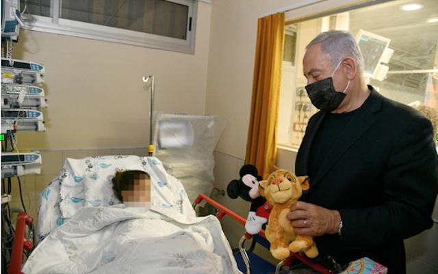 Le Premier ministre Benjamen Netanyahu visite des blessés à l'hôpital Wolfson de Holon. (Crédit photo : Haim Zach - GPO)