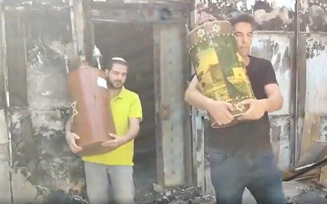 Des habitants de Lod récupèrent des rouleaux de la Torah indemnes dans les ruines d'une synagogue incendiée par des émeutiers arabes, le 12 mai 2021. (Capture d'écran : Twitter)