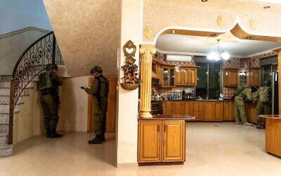 Des soldats israéliens cartographient la maison d'un Palestinien soupçonné d'avoir tiré sur trois israéliens depuis sa voiture, avant sa démolition éventuelle, dans le village de Turmus Ayya, en Cisjordanie, le 6 mai 2021. (Crédit : armée israélienne)