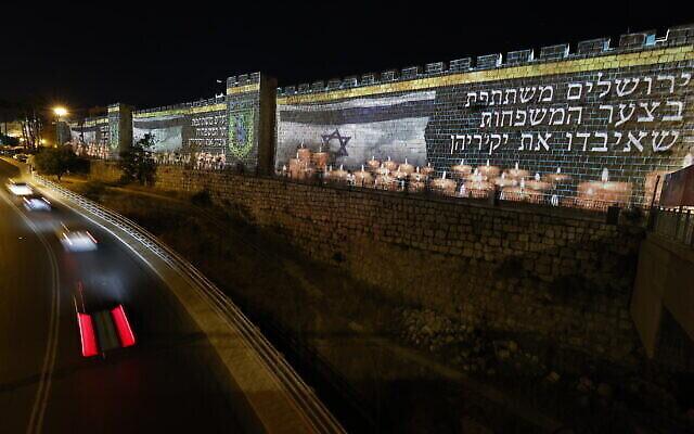 Les murs de la Vieille Ville de Jérusalem illuminés par le drapeau israélien et des bougies à la mémoire des 45 victimes tuées dans la bousculade au mont Meron lors des célébrations de Lag B'Omer, le 1er mai 2021. (Crédit : Yonatan Sindel / Flash90)