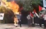Capture d'écran d'une partagée sur les médias sociaux montre un homme en Iran tenant un drapeau israélien géant auquel on a mis le feu, avant que les flammes ne le brûlent lui-même. (Twitter)