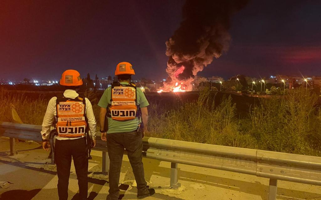 Des secouristes observent un incendie à Ramle causé par une roquette provenant de Gaza qui a atterri dans la ville, le 13 mai 2021. (Crédit : United Hatzalah)