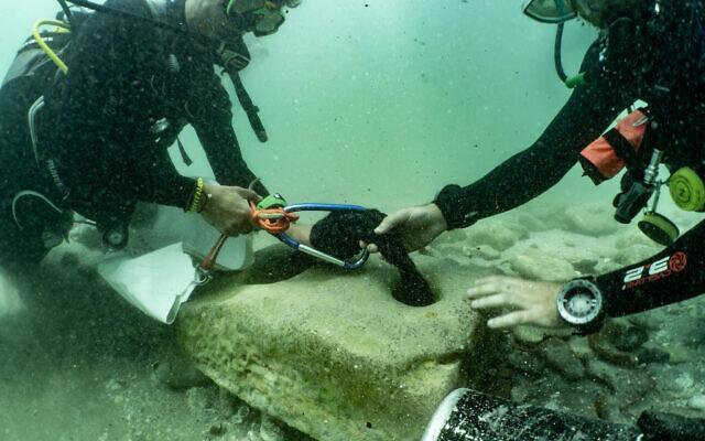 Des plongeurs, avec une ancienne ancre en pierre qui a été retrouvée sur le site archéologique de Tel Dor, dans le nord d'Israël, le 10 juin 2021. (Crédit : Amir Yurman de l'atelier maritime de l'Université de Haïfa)