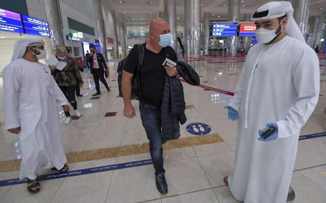 Un Israélien passe devant le personnel émirati après le contrôle des passeports à son arrivée de Tel Aviv à l'aéroport de Dubaï aux Émirats arabes unis, le 26 novembre 2020, lors du premier vol commercial régulier opéré par la compagnie aérienne à flydubai, suite à la normalisation des liens entre les EAU et Israël. (Crédit : Karim SAHIB / AFP)
