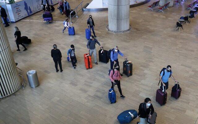 Des touristes et des Israéliens vaccinés, portant le masque pour se protéger de la COVID-19, lors de leur arrivée à l'aéroport Ben Gurion, près de Tel Aviv, le 23 mai 2021. (Crédit : JACK GUEZ / AFP)