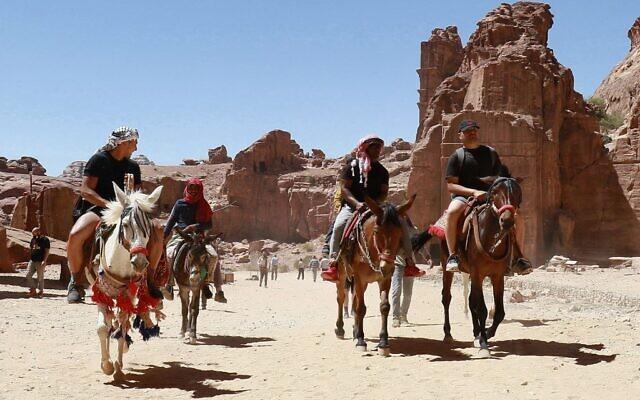 Des touristes montent à dos d'âne et de cheval lors de la visite de la cité antique de Petra, en Jordanie, le 27 mai 2021, après sa réouverture suite à la fermeture due à la pandémie de coronavirus Covid-19. (Crédit : Khalil MAZRAAWI / AFP)