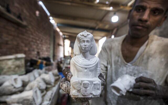Un artisan manipule une réplique moulée d'une figurine de buste de l'ancienne Égypte dans un atelier du quartier de Nazlet el-Semman, près de la nécropole des pyramides de Gizeh, dans la ville jumelle de la capitale égyptienne, Gizeh, le 6 juin 2021. (Crédit : Khaled DESOUKI / AFP)