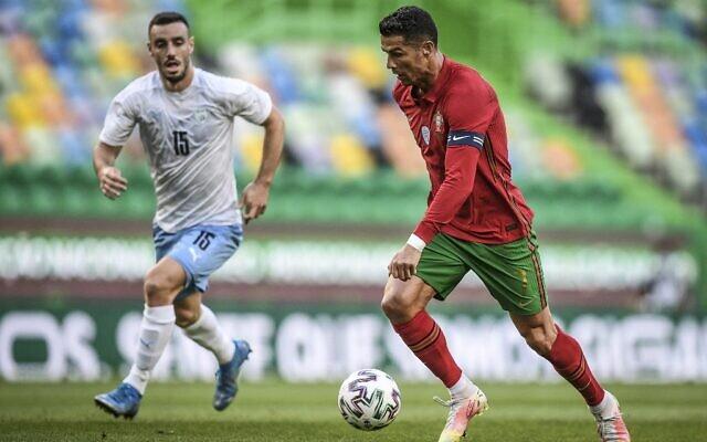 L'attaquant portugais Cristiano Ronaldo contrôle le ballon à côté du milieu de terrain israélien Neta Lavi (g) lors du match de football amical international entre le Portugal et Israël au stade José Alvalade à Lisbonne en préparation de la compétition de football UEFA EURO 2020, le 9 juin 2021. (Crédit : PATRICIA DE MELO MOREIRA / AFP)
