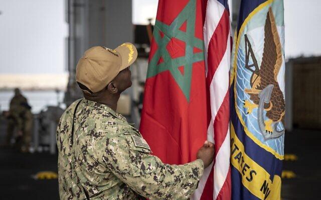 """Un membre de la marine américaine vérifie le drapeau marocain sur le navire de la marine américaine """"Hershel Woody Williams"""" lors de l'exercice militaire """"African Lion"""", le 11 juin 2021 dans la ville d'Agadir au Maroc. (Crédit : FADEL SENNA / AFP)"""