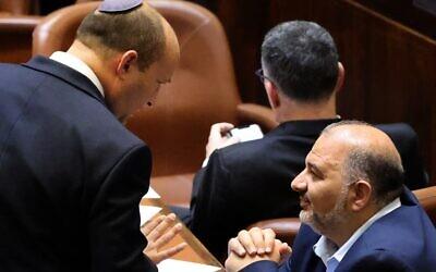 Le nouveau Premier ministre israélien Naftali Bennett (G) discute avec Mansour Abbas, chef du parti islamiste Raam, lors d'une session spéciale de vote pour le nouveau gouvernement à la Knesset, à Jérusalem, le 13 juin 2021. (Crédit : EMMANUEL DUNAND/AFP)