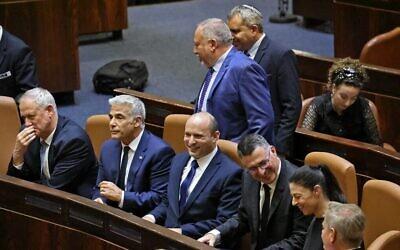 Les membres du nouveau gouvernement israélien (de gauche à droite), le ministre de la Défense Benny Gantz, le Premier ministre par alternance et ministre des Affaires étrangères Yair Lapid, le Premier ministre Naftali Bennett, le ministre de la Justice Gideon Saar, le ministre des Transports Merav Michaeli et le ministre de la Santé Nitzan Horowitz, regardent, assis dans la salle de la Knesset, tandis que (derrière C) le ministre des Finances Avigdor Liberman après une session spéciale pour voter sur un nouveau gouvernement à la Knesset à Jérusalem, le 13 juin 2021. (Crédit : EMMANUEL DUNAND / AFP)