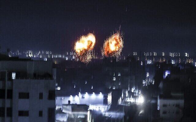 Des explosions illuminent le ciel nocturne au-dessus des bâtiments de la ville de Gaza, alors que les forces israéliennes bombardent l'enclave palestinienne, tôt le 16 juin 2021. (Crédit