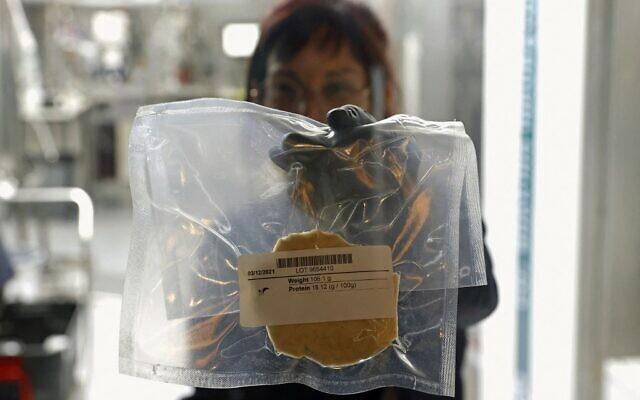 Un technicien présente de la viande de poulet cultivée en laboratoire dans un sac sous-vide, dans les locaux de la startup de technologie alimentaire SuperMeat àNess Ziona, le 18 juin 2021. (Crédit : JACK GUEZ / AFP)