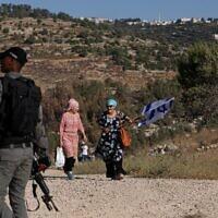 Des partisans du mouvement pro-implantation défilent avec un drapeau israélien sur une colline à proximité de l'implantation de Bat Ayin en Cisjordanie, le 21 juin 2021. (Crédit : Emmanuel DUNAND / AFP)