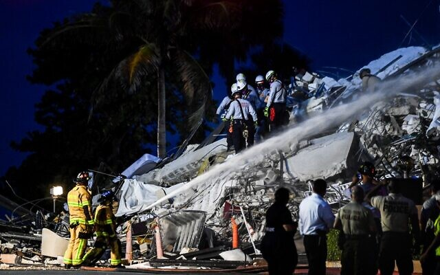 Le personnel de recherche et de sauvetage travaille sur un bâtiment partiellement effondré à Surfside, Miami Beach, le 24 juin 2021. (Crédit : CHANDAN KHANNA / AFP)
