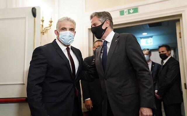 Le secrétaire d'État américain Antony Blinken, au centre, salue le ministre des Affaires étrangères israélien Yair Lapid à Rome, lors d'une rencontre, le 27 juin 2021. (Crédit :  Andrew Harnik/Pool/AFP)