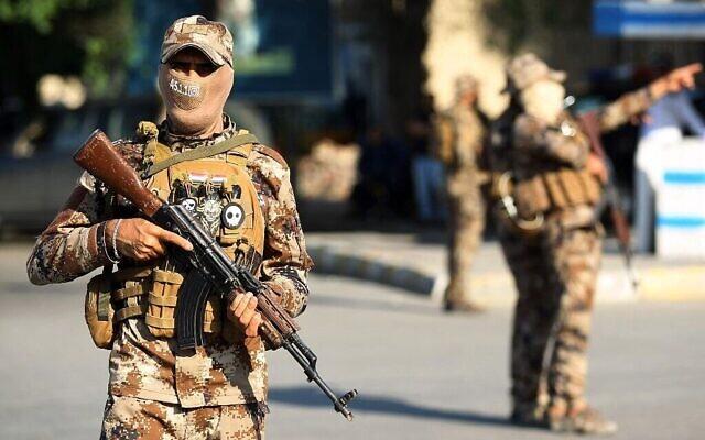 Illustration : Des combattants paramilitaires de Hashed al-Chaabi montent la garde lors d'une procession funéraire dans la capitale irakienne de Bagdad, le 26 octobre 2019. (Crédit : Ahmad Al-Rubaye/AFP)
