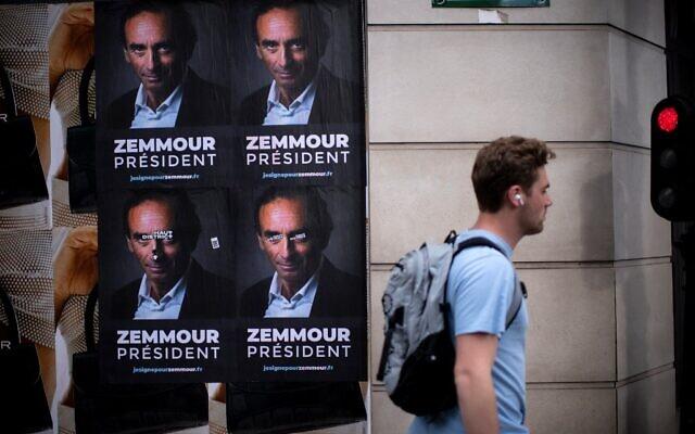 Un passant devant des pancartes collées par des membres du comité de soutien à Eric Zemmour dans une rue de Paris, le 28 juin 2021. (Crédit : Olivier MORIN / AFP)