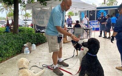 Jay Harris, bénévole de United Cajun Navy, nourrit les chiens qu'il a amenés pour la thérapie à Surfside, en Floride, le 28 juin 2021. (Crédit : Chris STEIN / AFP)